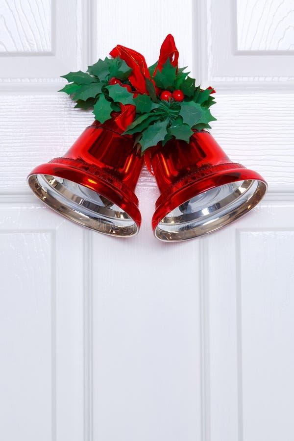 Weihnachtsglocken auf einer weißen Tür stockfotografie