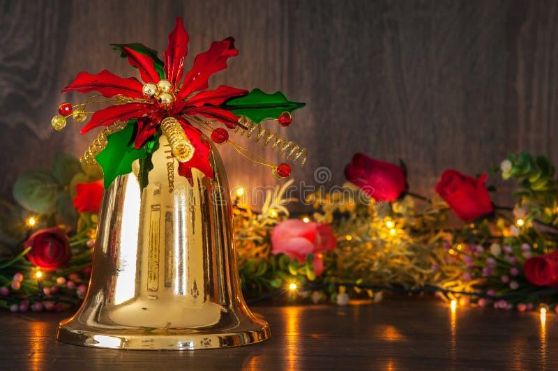 Weihnachtsgoldene Glocke mit den roten und grünen Blumen lizenzfreie stockfotografie