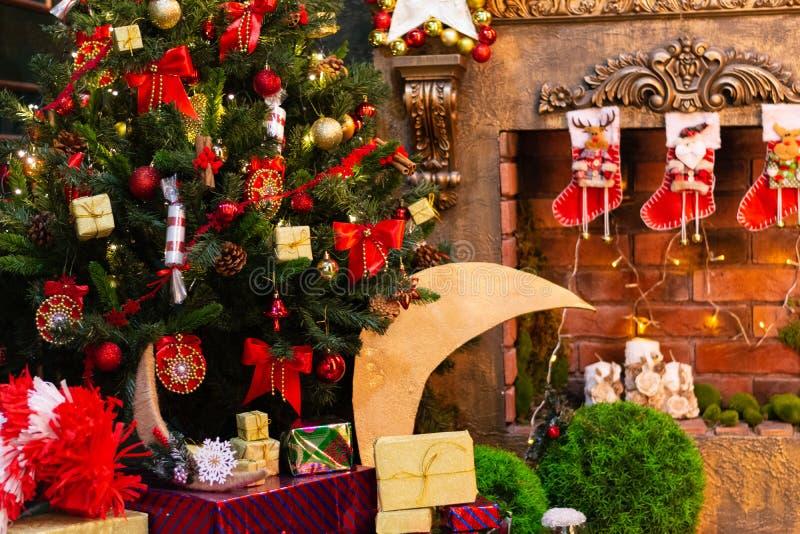 Weihnachtsgrüner Tannenbaum verziert mit Spielwaren und einem Kamin stockfotografie