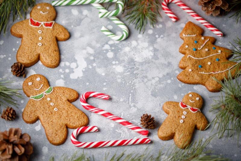 Weihnachtsgrauer Hintergrund mit Stechpalmenniederlassungs-, -lutscher-, -tannenbaum- und -lebkuchenplätzchen Der Rahmen für Ihre stockfotografie