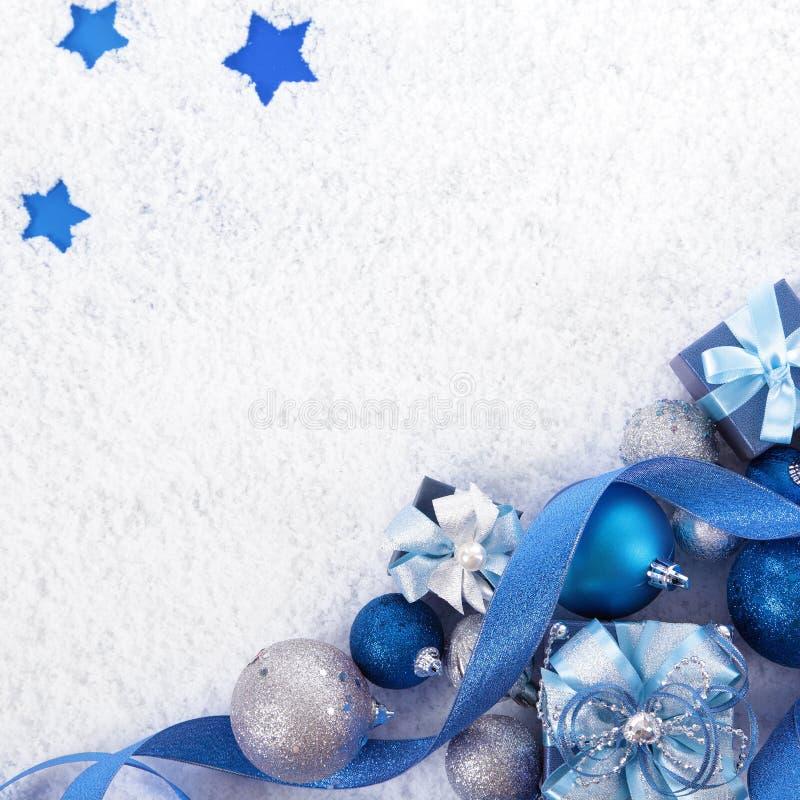 Weihnachtsgrenze mit den blauen und silbernen Dekorationen auf dem Schnee Quadrat lizenzfreie stockbilder
