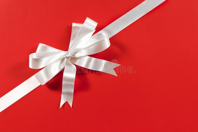 Weihnachtsgrenzrahmengeschenk-Bandbogen, roter Papierhintergrund, Eckdiagonale stockfotografie