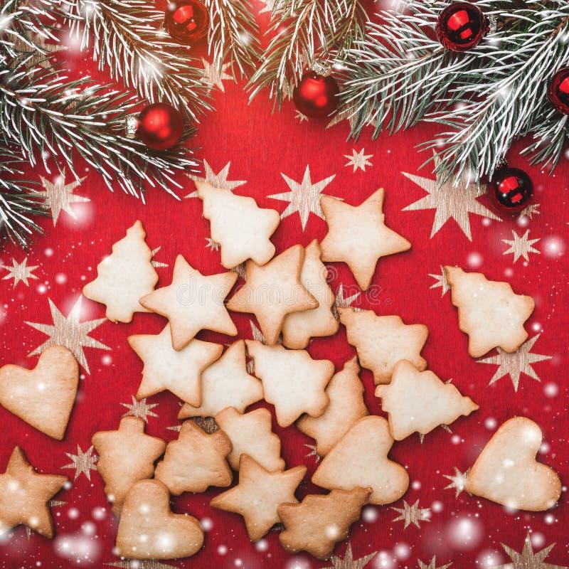 Weihnachtsgrußkarte, roter Hintergrund mit Sternen mit Keksen von verschiedenen Formen Tannenzweige mit roten Bällen stockfotos