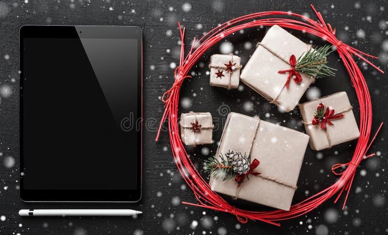 Weihnachtsgrußkarte, schwarzes ipad, zum einer Mitteilung für geliebte und die liebe, symbolische Feriengeschenke des Winters zu  stockfoto