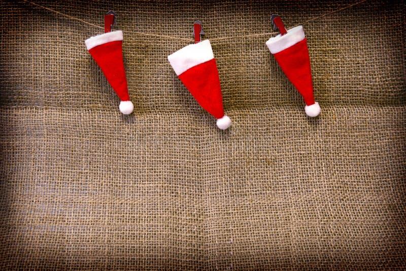 Weihnachtshüte, die am braunen Stoffhintergrund hängen lizenzfreies stockfoto