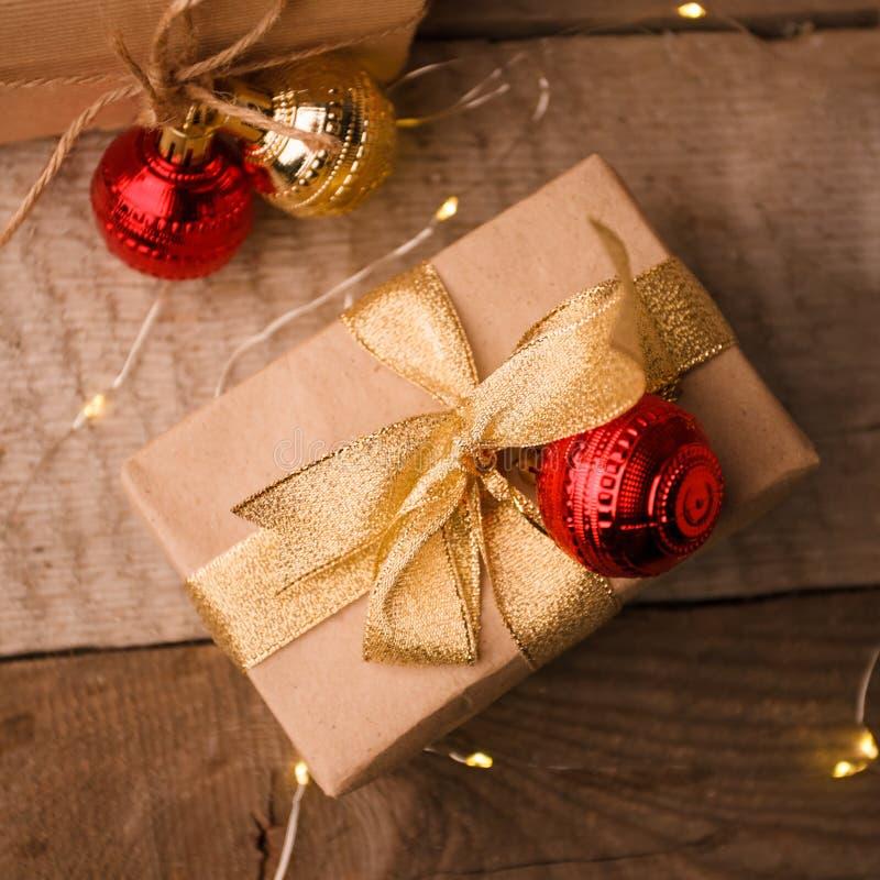 Weihnachtshandgemachte Geschenkbox verziert mit Kraftpapier und rotem Goldkugel- und handgemachtemplätzchenstern auf hölzernem Hi lizenzfreie stockfotos