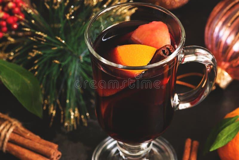 Weihnachtsheißer Glühwein in einem Glasbecher mit orange Gewürzen und Fruchtnahaufnahme Selektiver Fokus lizenzfreies stockbild
