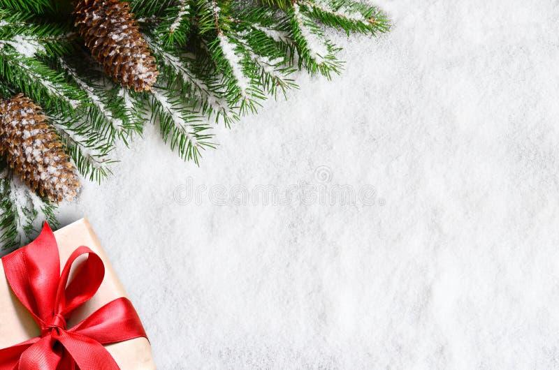 WeihnachtshHintergrund, grüngrüne Kiefer-Äste, Zapfen und Geschenkbox auf Schneeuntergrund Kreative Zusammensetzung mit Rand- und stockbild
