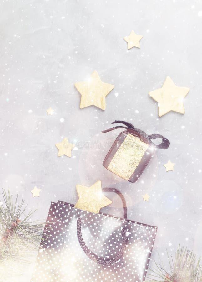 Weihnachtshintergrund: Einkaufstasche, schwarze Geschenkbox und Goldsterne unter Schnee stock abbildung