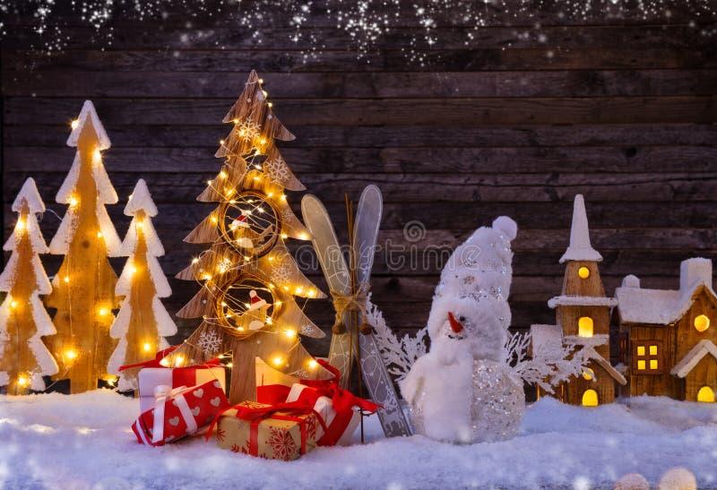 Weihnachtshintergrund mit belichtetem hölzernem Dorf und Schneemann lizenzfreies stockbild