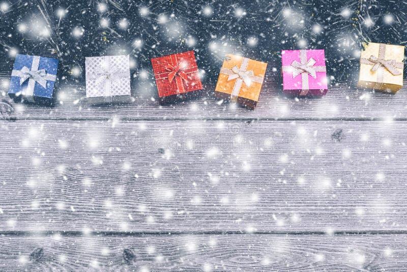 Weihnachtshintergrund mit Dekorationen, Geschenkboxen, Baumasten und rotem Flitter auf hölzernem Hintergrund stockbilder