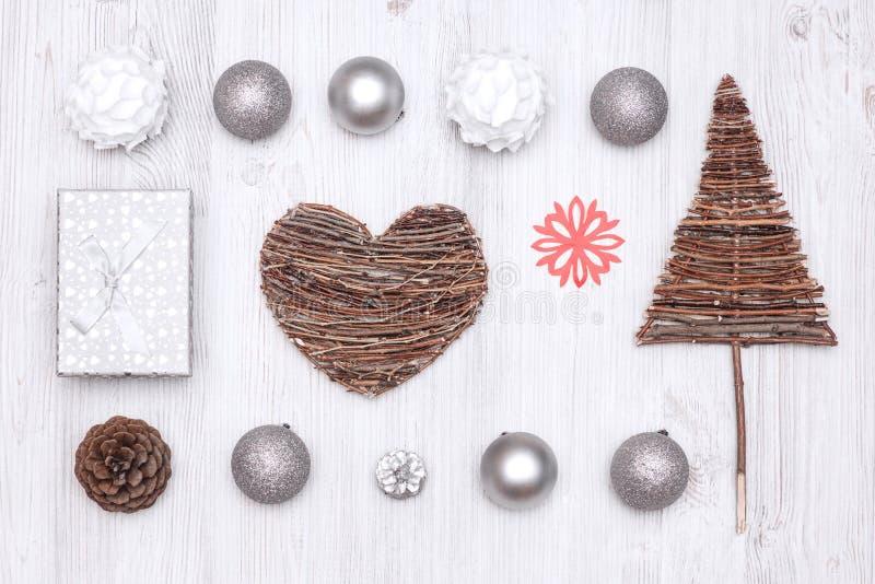 Weihnachtshintergrund mit einer roten Schneeflocke, einer Geschenkbox, einem Herzen und einer Tanne von Niederlassungen stockbilder