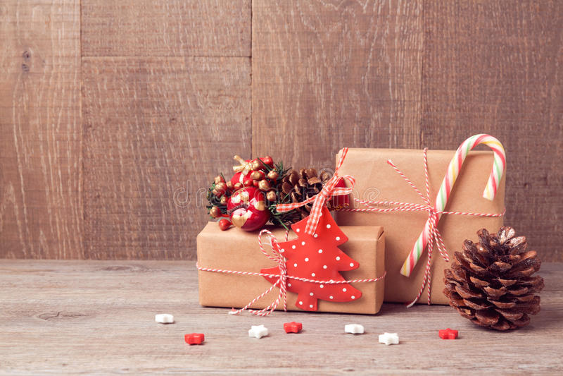 Weihnachtshintergrund mit Geschenkboxen und rustikalen Dekorationen auf Holztisch lizenzfreie stockfotografie