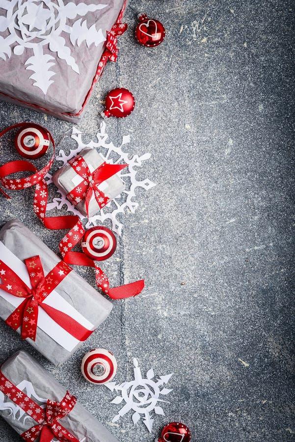 Weihnachtshintergrund mit geschnittenen Papierschneeflocken, Geschenkboxen und Dekorationen, Draufsicht stockbild