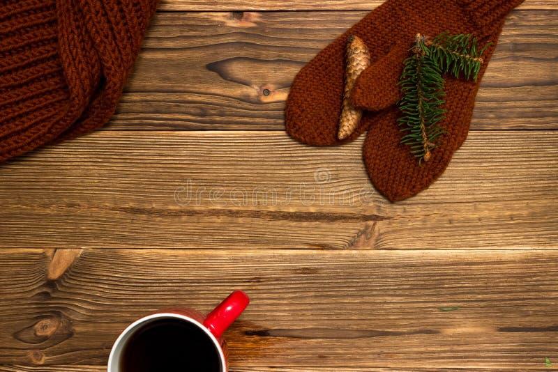 Weihnachtshintergrund mit gestrickten Handschuhen und einem Tasse Kaffee stockfotografie