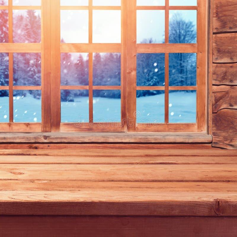 Weihnachtshintergrund mit hölzerner leerer Tabelle über Fenster und Winternatur gestalten landschaftlich Winterurlaubhausinnenrau stockfotografie