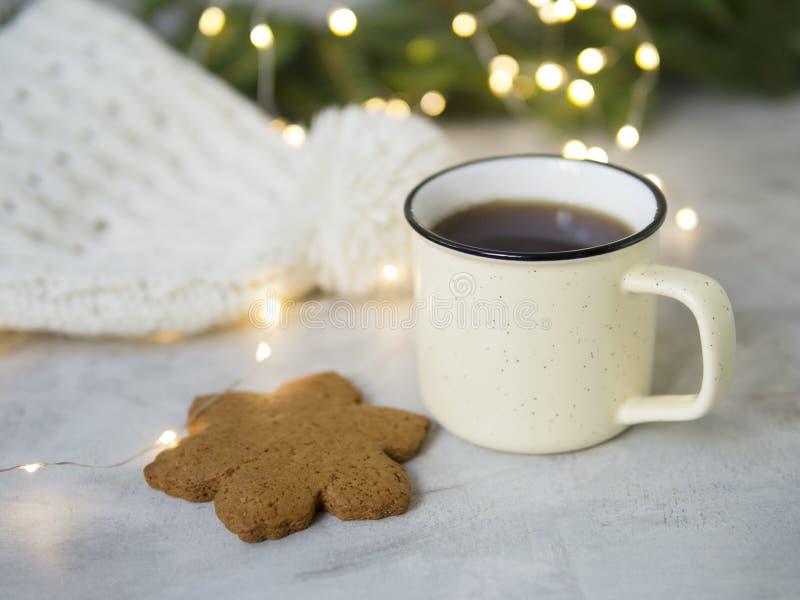 Weihnachtshintergrund mit Lebkuchenplätzchen, Tasse Tee Gemütlicher Abend, Becher des Getränks, Weihnachtsdekorationen, Lichtgirl lizenzfreie stockbilder