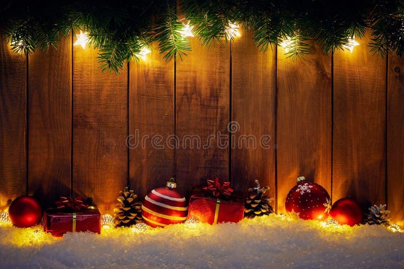 Weihnachtshintergrund mit Niederlassungen und rotem Flitter auf hölzernem Brett stockbilder