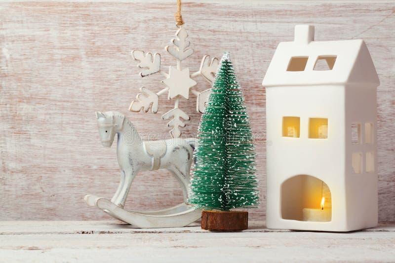 Weihnachtshintergrund mit rustikalen Dekorationen, Hauskerze, Kiefer und Schaukelpferd lizenzfreies stockbild