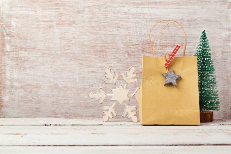 Weihnachtshintergrund mit selbst gemachter Geschenktasche und rustikalen Dekorationen stockfoto