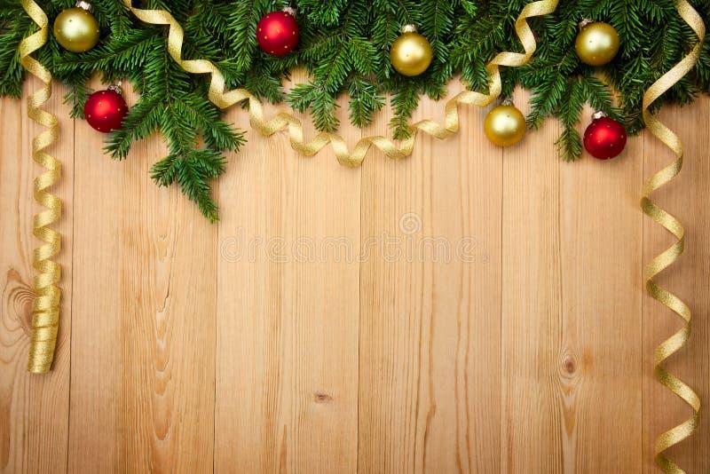 Weihnachtshintergrund mit Tannenbaum, Flitter und Bändern auf Holz stockbild