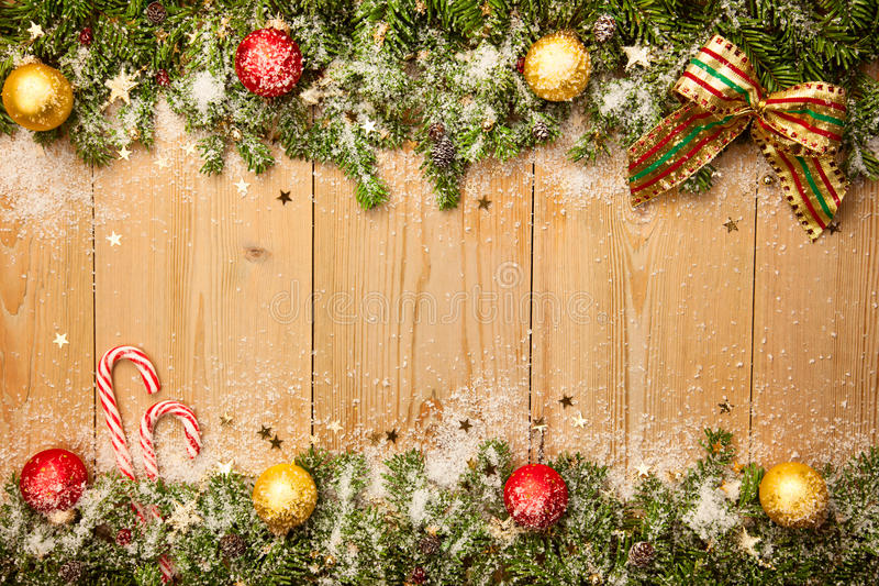 Weihnachtshintergrund mit Tannenbaum, Süßigkeiten und Flitter mit Schnee stockfotografie