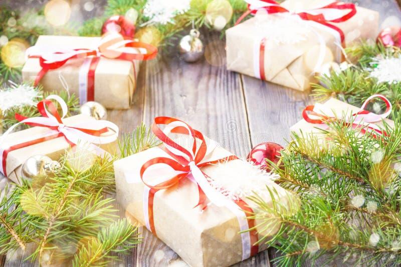 Weihnachtshintergrund mit Tannenbaum und -dekorationen und Geschenkboxen auf dem hölzernen Brett verziert mit Schnee stockfotos