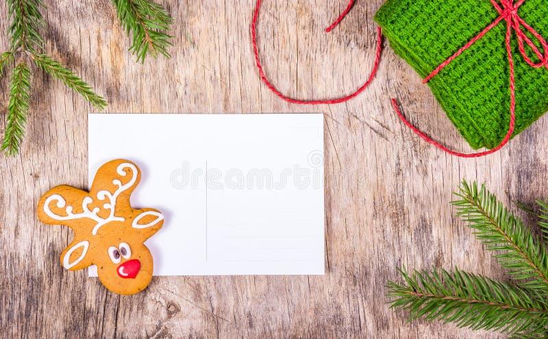 Weihnachtshintergrund mit Tannenbaum und leerer Grußkarte Vorbereiten für Weihnachten Gemalter Lebkuchen und gestricktes Geschenk lizenzfreie stockfotos