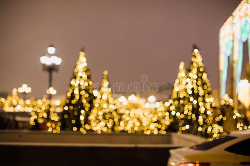 Weihnachtshintergrund mit unfocused Weihnachtsbaum bis zum Nacht Stadt verziert mit Weihnachtslichtern stockfotografie