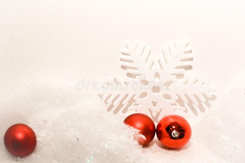 Weihnachtshintergrund mit weißer Schneeflocke und roten Verzierungen stockbilder
