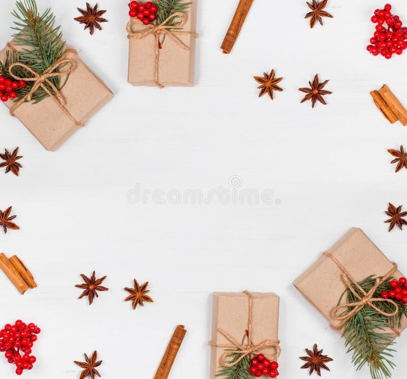 Weihnachtshintergrund mit Weihnachtsgeschenk, Tannenzweige, Kiefernkegel, Schneeflocken, rote Dekorationen stockbild