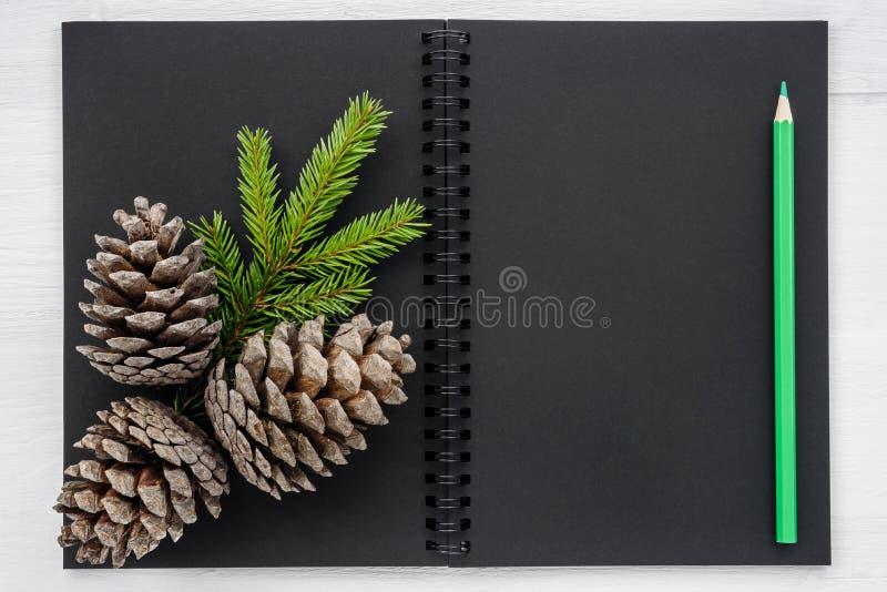 Weihnachtshintergrund - Notizbuch und Weihnachtsdekorationen stockfotos