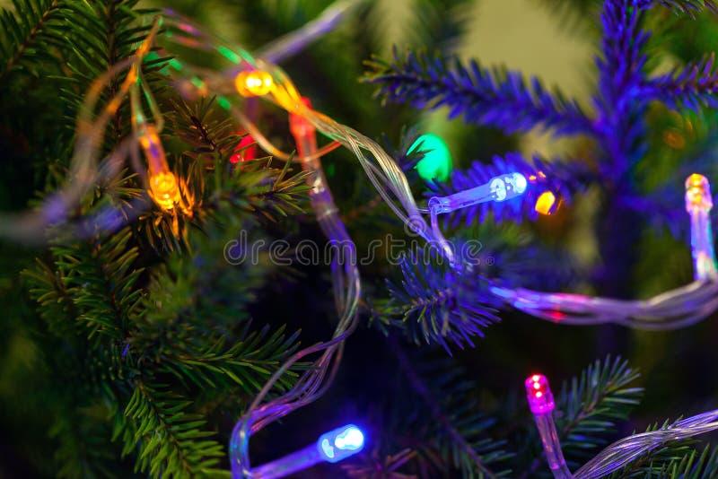 Weihnachtshintergrund, Weihnachtsbaum mit bunter Laternennahaufnahme Die glühenden Lichter, neues Jahr stockfotos