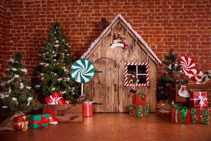 Weihnachtsinnenraum mit Holzhaus, Süßigkeit, Baum und Geschenken Keine Leute Gelbe und rote Farben stockbilder