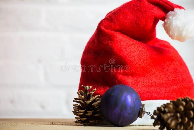 Weihnachtsjahreszeit, rustikale Dekoration, Sankt-Hüte mit Kiefernkegeln mit Lichtern, Goldweihnachtsball-Dekorationshintergrund lizenzfreie stockfotografie