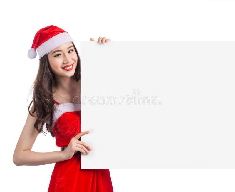 Weihnachtsjunge asiatische Frau, die leeres Anschlagtafelfahnenzeichen zeigt lizenzfreies stockfoto