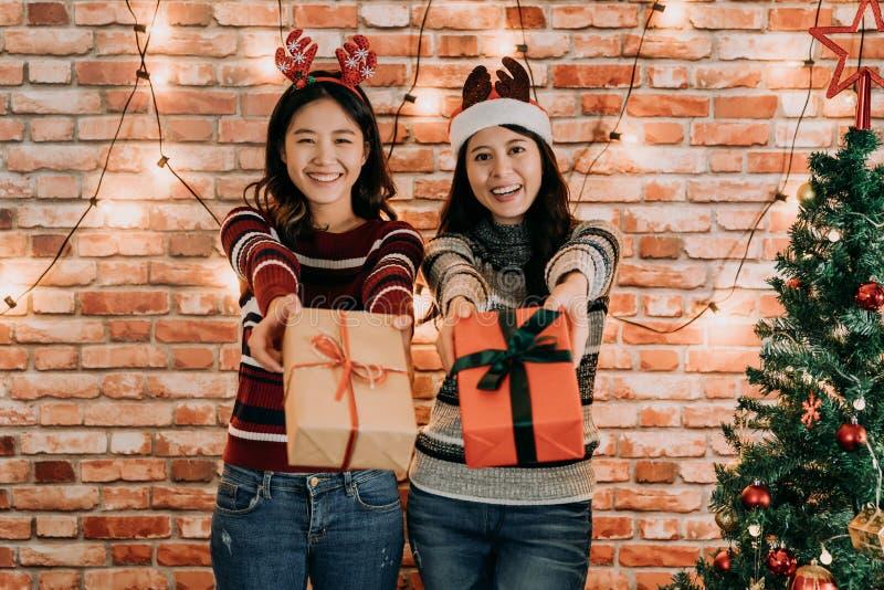 Weihnachtsjunge Freundinnen, die Geschenke geben stockfotos
