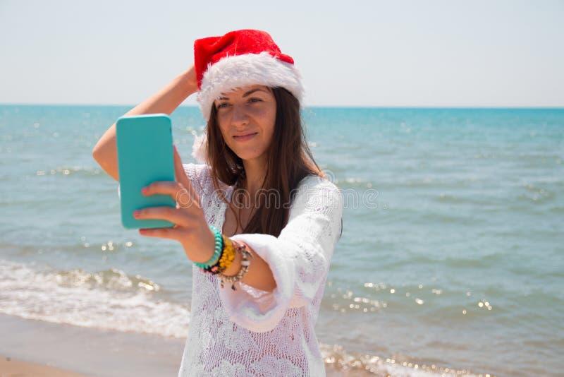Weihnachtsjunge lächelnde Frau in rotem Sankt-Hut, der Bildselbstporträt auf Smartphone am Strand über Seehintergrund nimmt geton stockfoto
