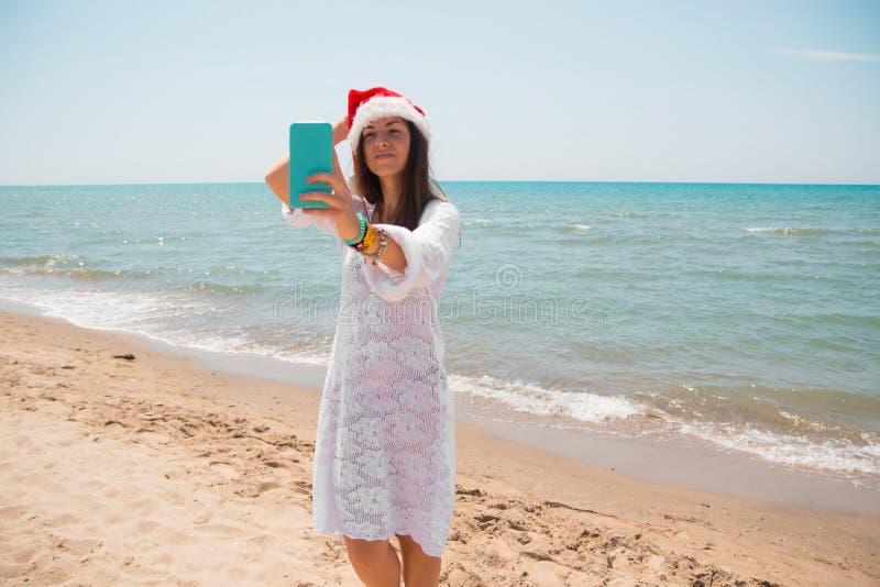 Weihnachtsjunge lächelnde Frau in rotem Sankt-Hut, der Bildselbstporträt auf Smartphone am Strand über Seehintergrund nimmt geton lizenzfreies stockfoto
