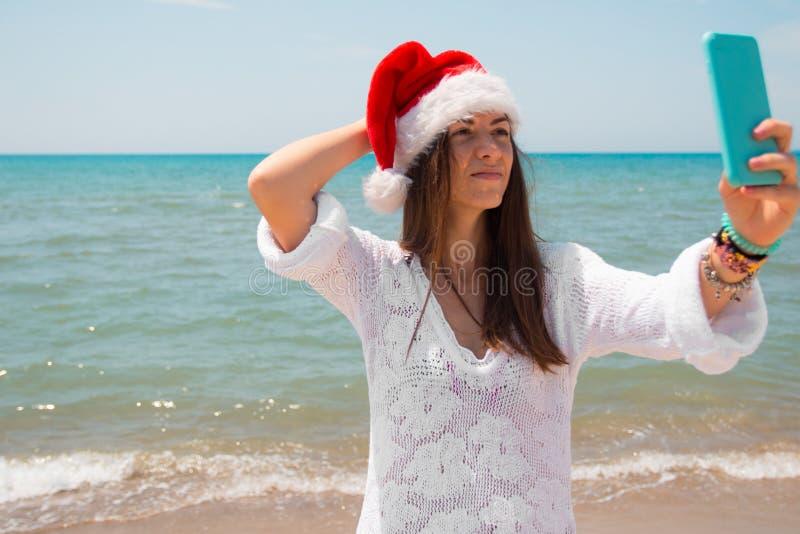 Weihnachtsjunge lächelnde Frau in rotem Sankt-Hut, der Bildselbstporträt auf Smartphone am Strand über Seehintergrund nimmt geton lizenzfreies stockbild