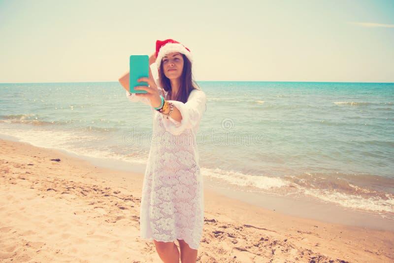 Weihnachtsjunge lächelnde Frau in rotem Sankt-Hut, der Bildselbstporträt auf Smartphone am Strand über Seehintergrund nimmt geton lizenzfreie stockbilder