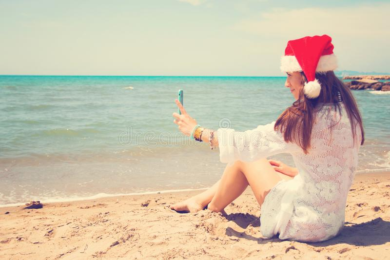 Weihnachtsjunge lächelnde Frau in rotem Sankt-Hut, der Bildselbstporträt auf Smartphone am Strand über Seehintergrund nimmt geton stockbild