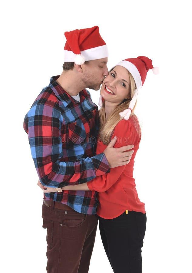 Weihnachtsjunge schöne Paare in Sankt-Hüten beim Liebeslächeln glücklich zusammen, umarmend süß stockbilder