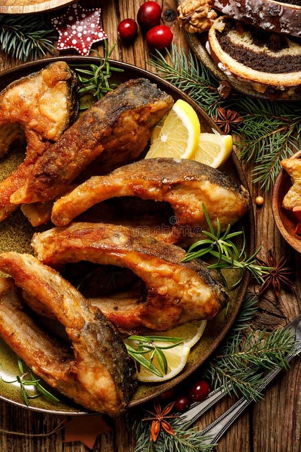 Weihnachtskarpfen, gebratene Karpfenfischscheiben auf einer keramischen Platte, Abschluss oben, Draufsicht Traditioneller Weihnac lizenzfreies stockfoto