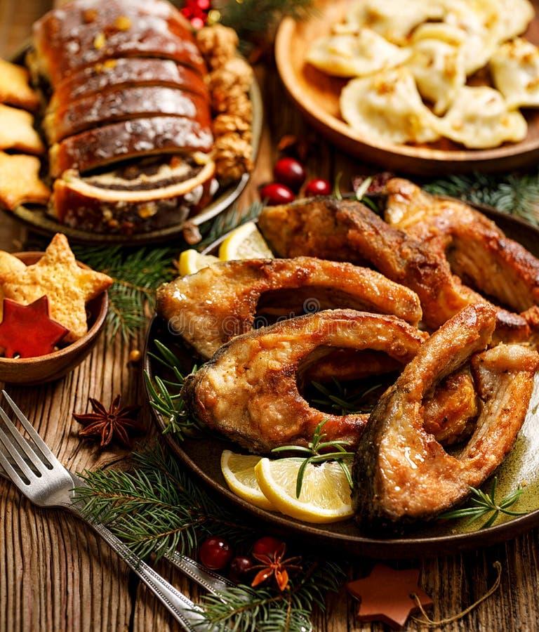 Weihnachtskarpfen, gebratene Karpfenfischscheiben auf einer keramischen Platte, Abschluss oben Traditioneller Weihnachtsabendstel stockfotos