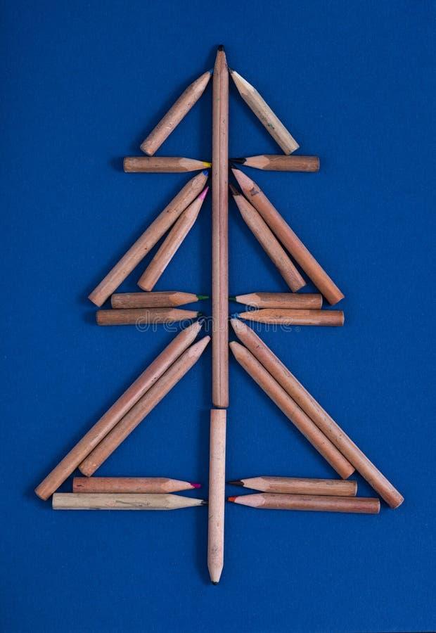 Weihnachtskarte mit bunten Bleistiften als Weihnachtsbaum - blauem Papphintergrund lizenzfreies stockbild