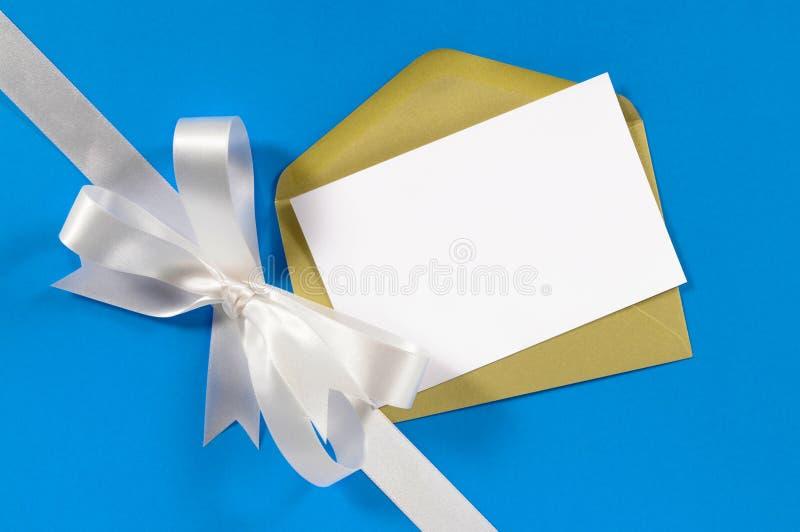 Weihnachtskarte mit Geschenkbandbogen im weißen Satin auf Hintergrund des blauen Papiers, Kopienraum stockfotografie