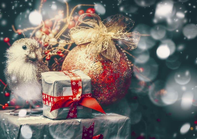 Weihnachtskarte mit schön verpackten Geschenken, Weinleseweihnachtsball mit Band und Vogel auf dem dunklen Schneehintergrund, Ret stockfoto
