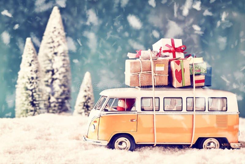 Weihnachtskarte mit Weinleseauto und vielen Weihnachtsgeschenken in der winterlichen Landschaft stockfoto