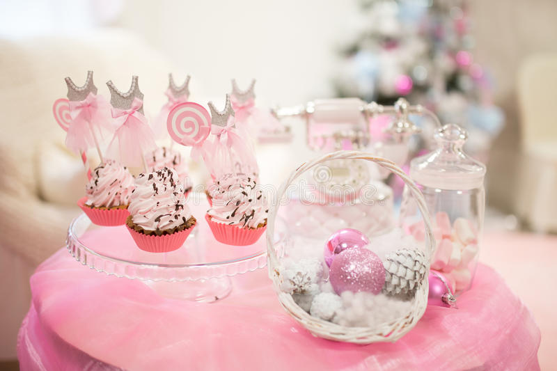 Weihnachtskarte, süße rosa Tabelle mit Kuchenkegeln, auf einem Weihnachtsbaumhintergrund stockfoto